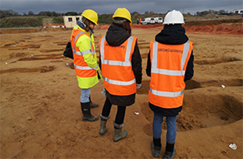 people visiting a commercial excavation site