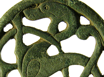 copper alloy mount with openwork decoration depicting an animal