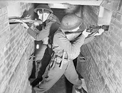 staged wartime photo of two armed men at windows in narrow gunhouse