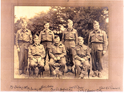 war photo of four officers standing with three Home Guard men sitting