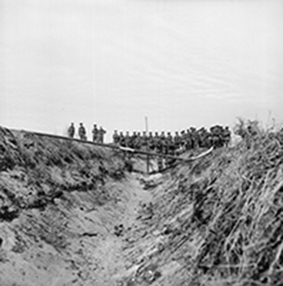 war photo of soldiers watching explosive device in trench